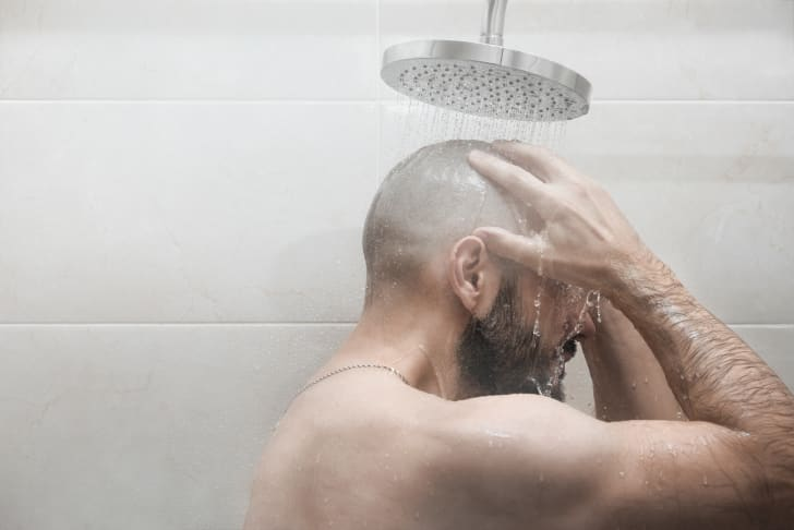 A man from the shoulders up in a hot shower