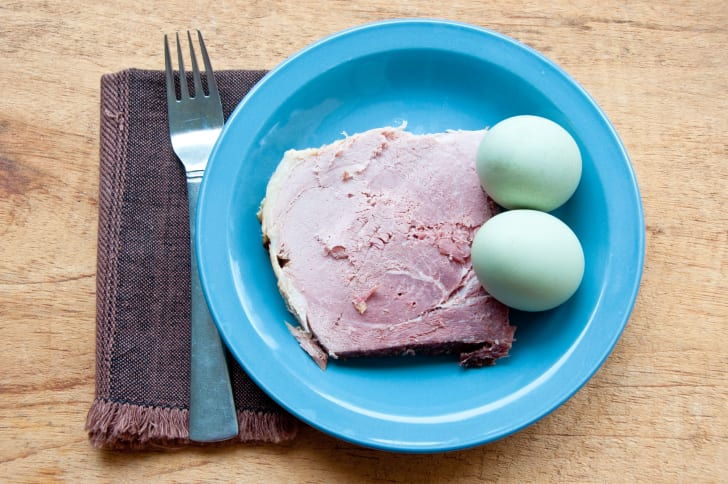 A blue plate with green eggs and ham