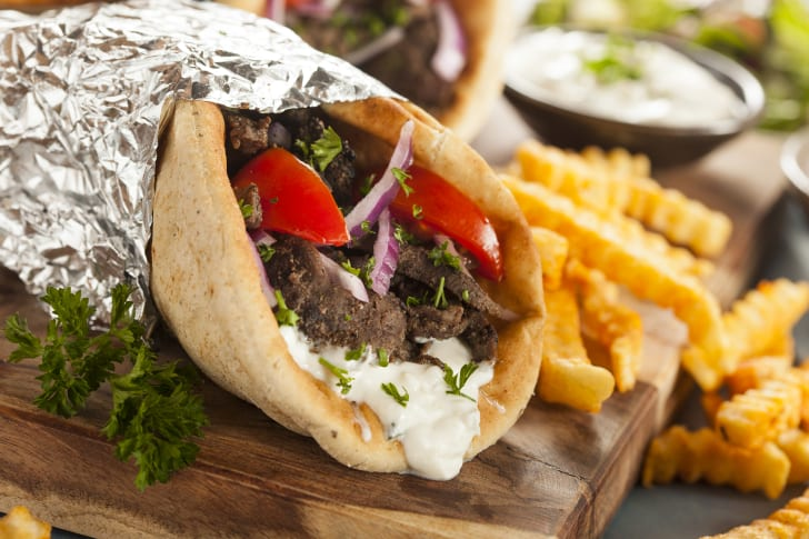 Close up of a gyro sandwich with french fries