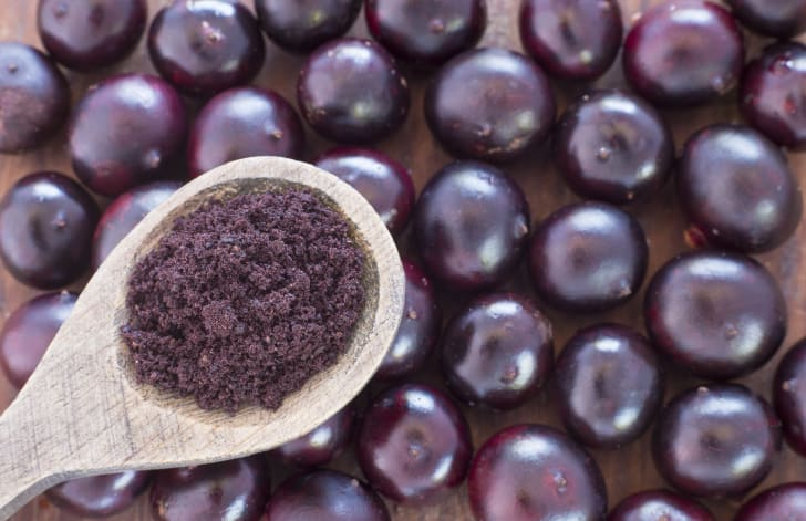 A spoon of acai powder over some acai berries
