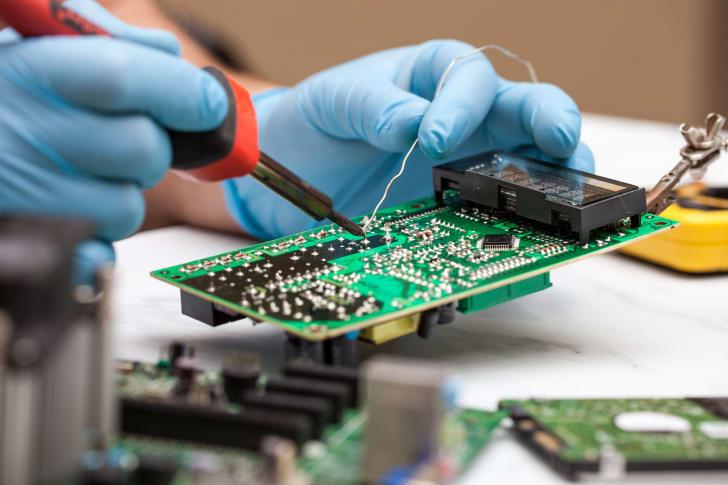 Gloved hands solder a microprocessor