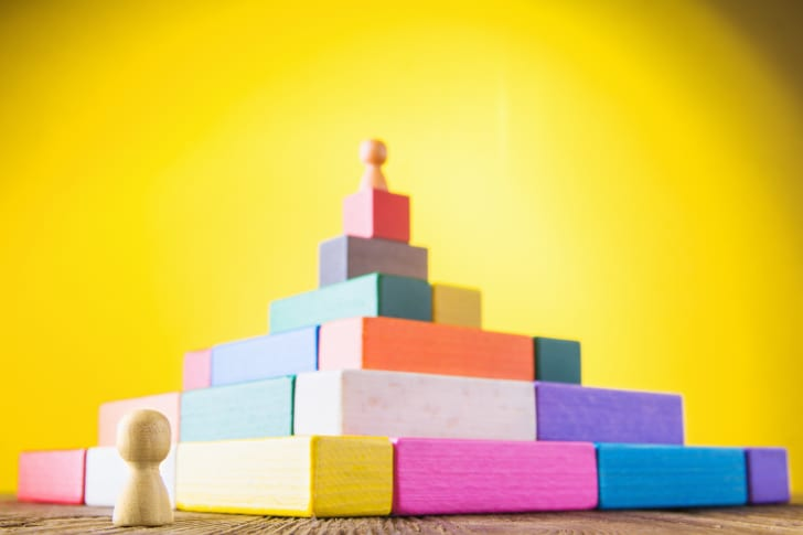 A colored peg stands on a pyramid of colored blocks while another peg stands in foreground