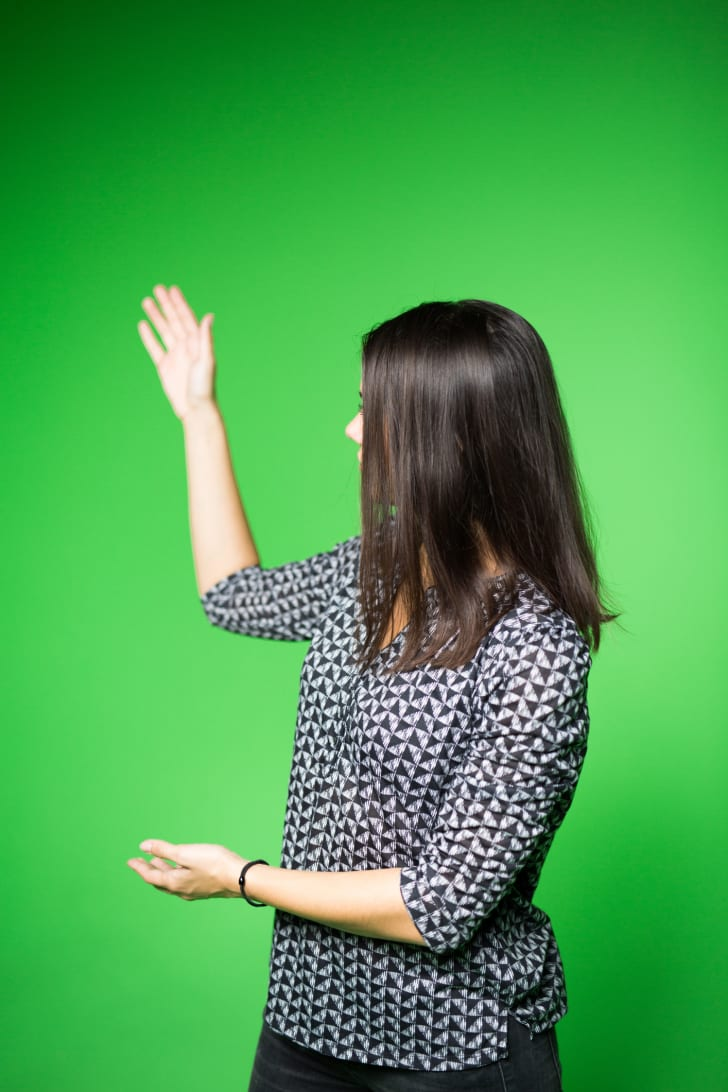 A meteorologist working in front of a green screen.