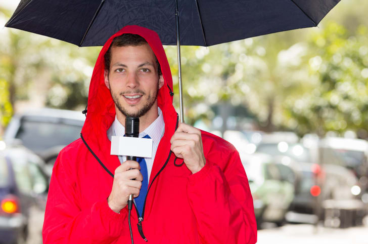 A weatherman reporting during a storm.