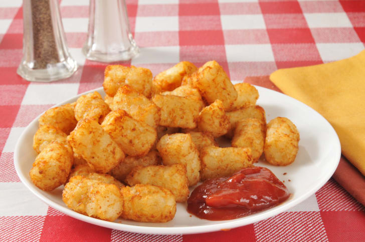 Tater tots on a plate served with ketchup.