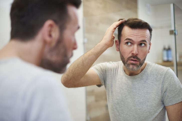 man touches receding hairline