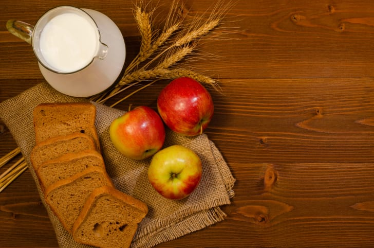 Slices of rye bread, a jug of milk, apples and ears of corn on sackcloth, wooden table