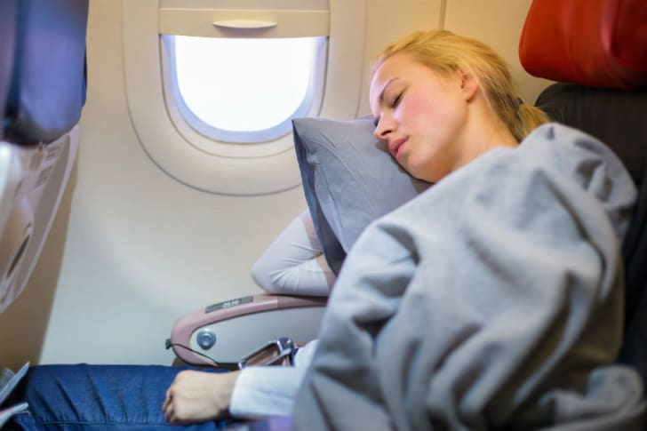 A woman is pictured sleeping in an airplane