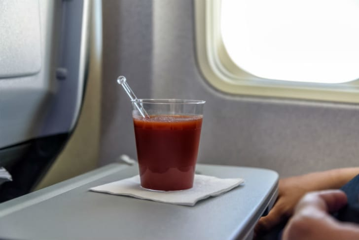 A cup of tomato juice on an airplane serving tray is pictured