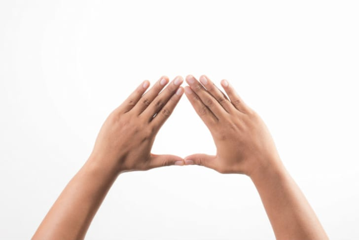 A pair of hands is pictured making a triangle shape