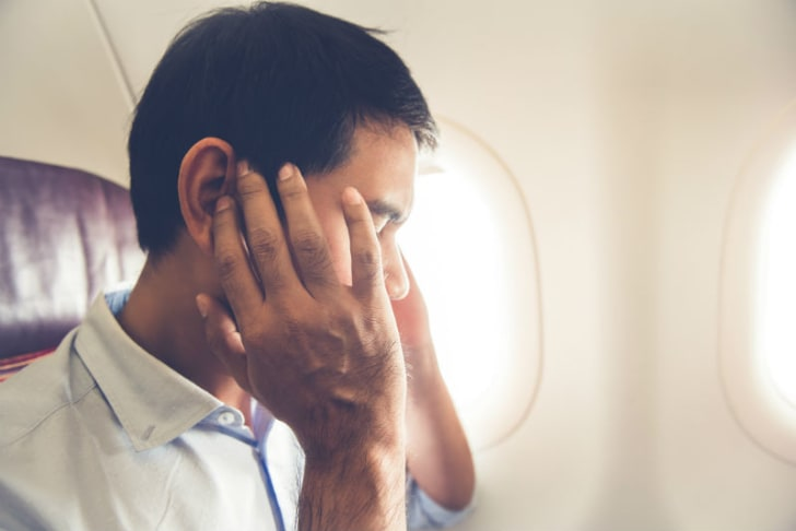 A man is pictured holding his ears on an airplane