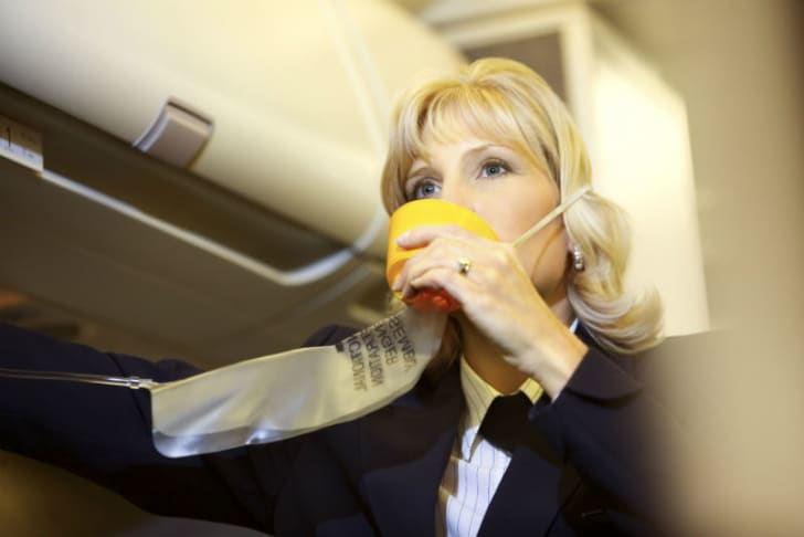 A flight attendant is pictured demonstrating an oxygen mask
