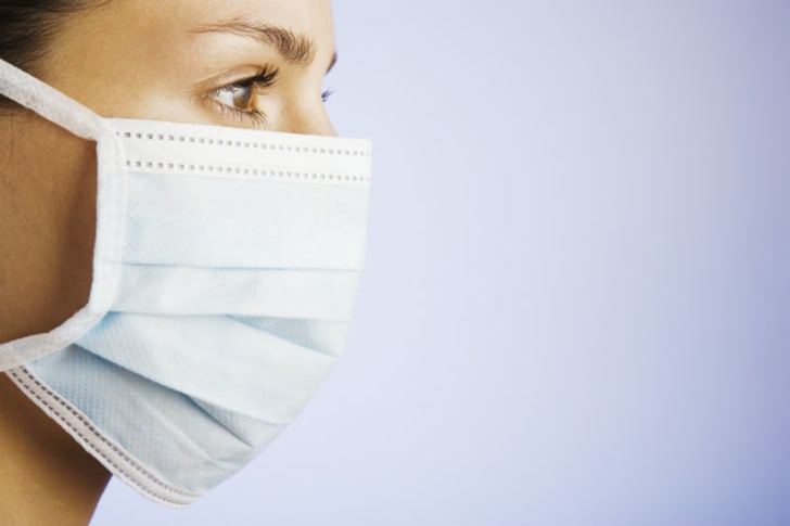 A woman wearing a surgical mask is pictured