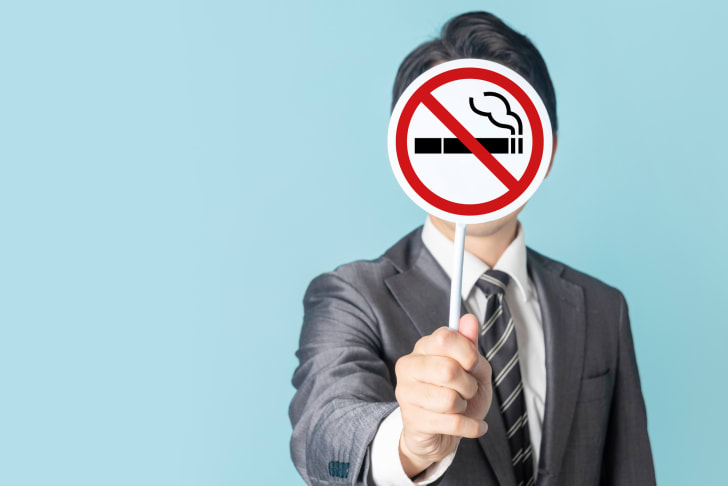 Photo of a businessman in suit holding a no smoking sign against a blue background