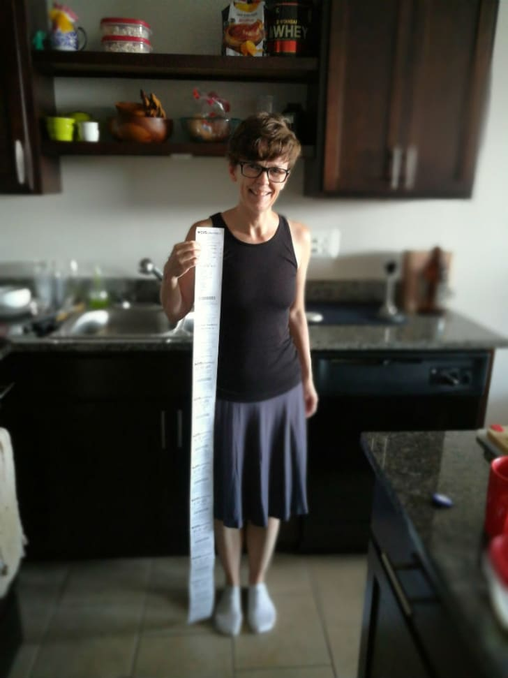 A woman is pictured holding up a CVS receipt