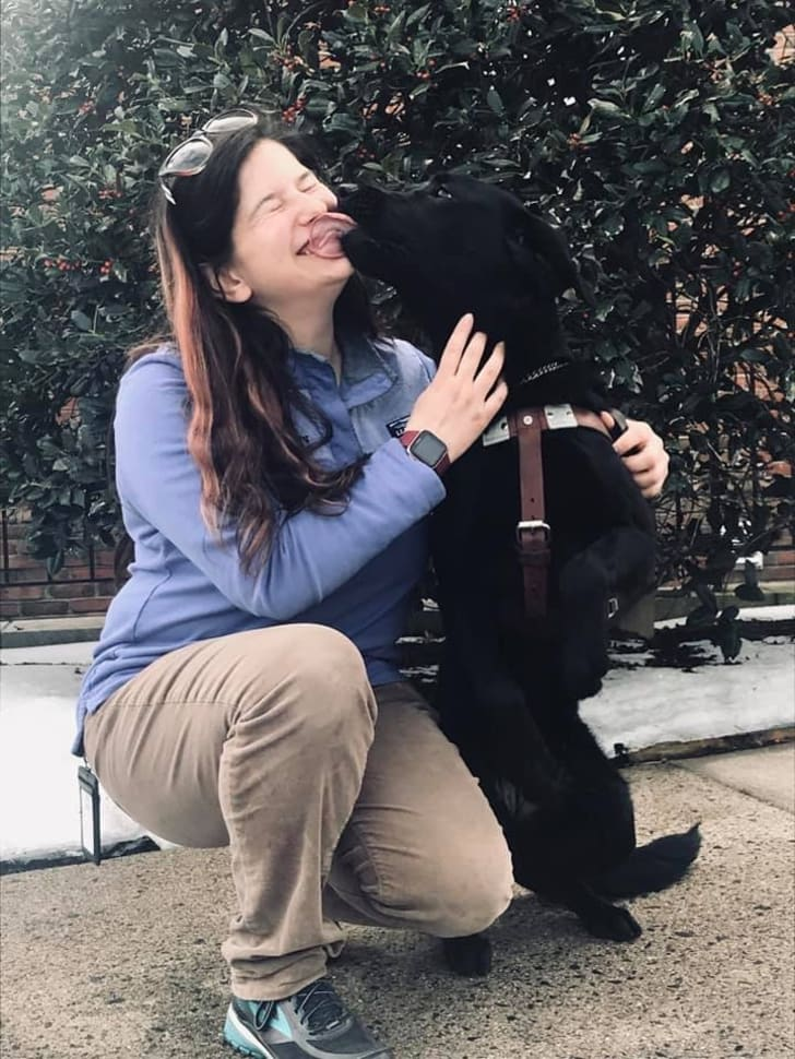 Seeing Eye instructor with a black Lab.