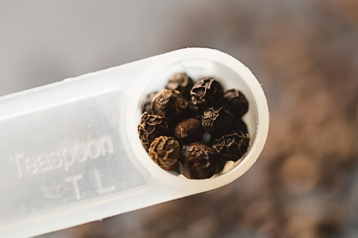 Black peppercorns in a measuring spoon