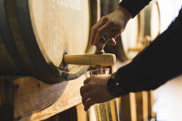Man pouring wine out of a barrel