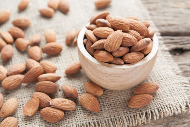 A group of almonds in wood bowl atop a rustic table