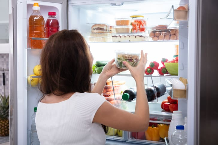 Woman putting food container in the fridge
