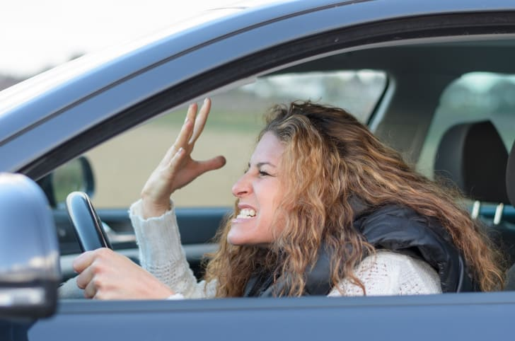 A woman screaming in her car.