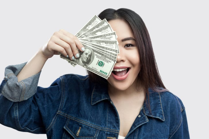 A woman holding money in front of her face.