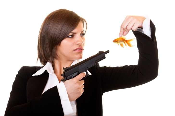 A woman holding a gun to a goldfish.