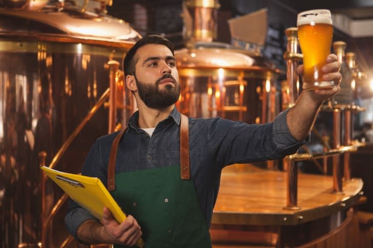 A brewer examines a pint of beer