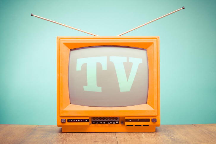 Retro orange TV receiver on table front mint green wall background