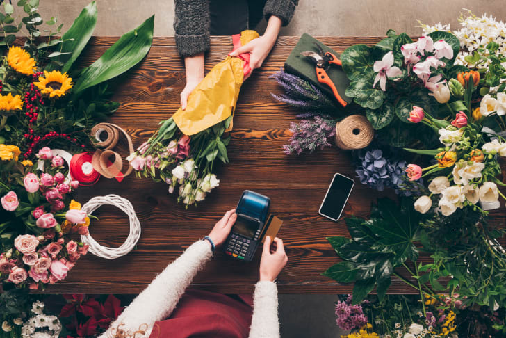 Cropped image of a customer paying with credit card for bouquet