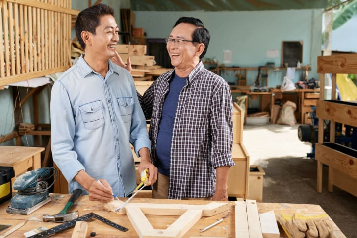 Vietnamese senior man and his adult son making furniture in small garage workshop