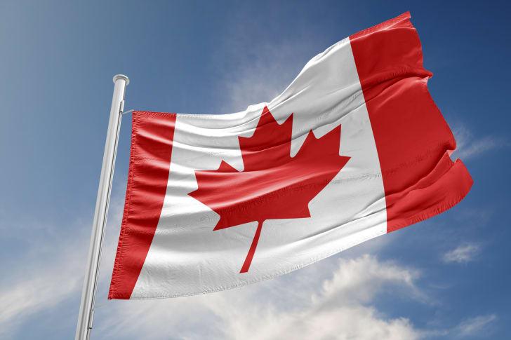 A Canadian flag against a bright blue sky
