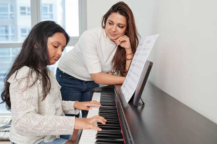Young woman watching a girl play piano