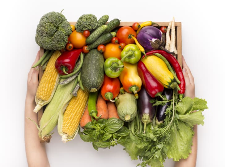 Woman holding big wooden box with fresh vegetables
