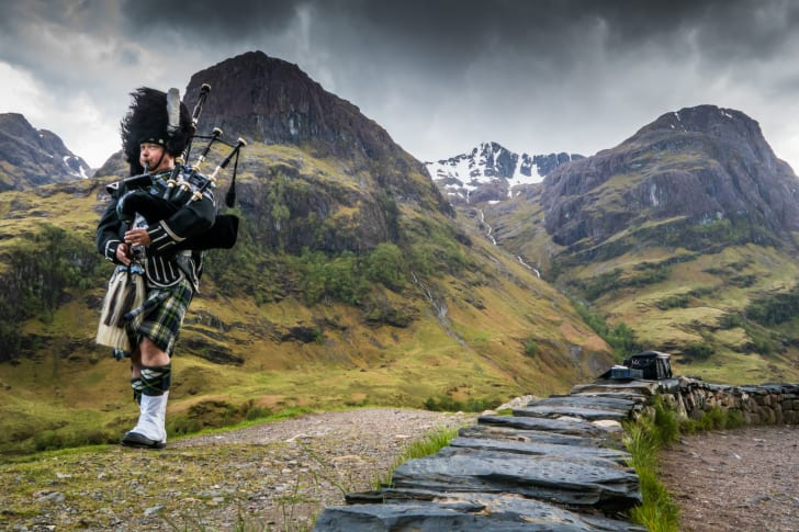 Traditional bagpiper in the Scottish Highlands