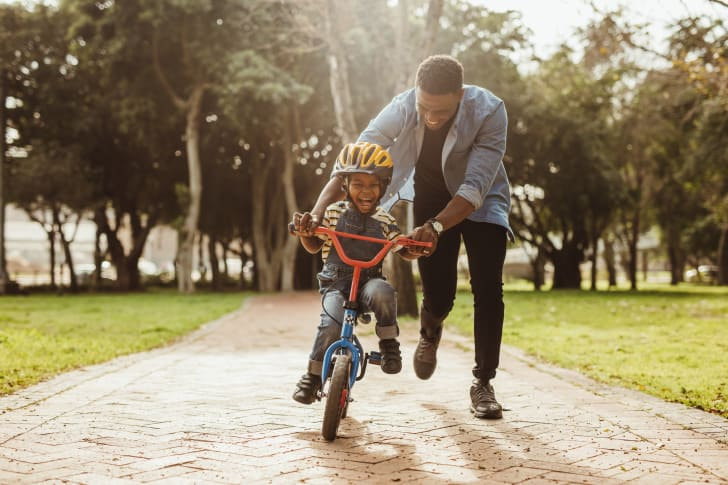 Father teaching his son cycling at a park