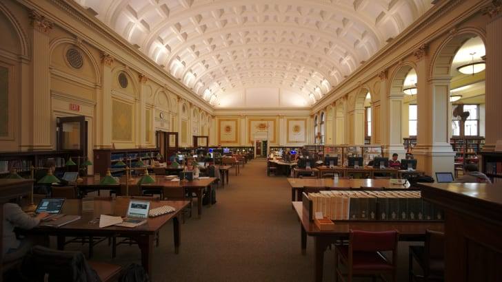 People working at desks inside a library