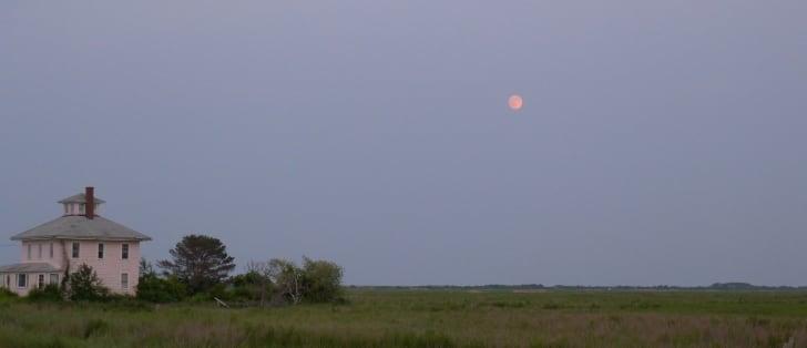 A pink house beneath a full moon at dusk