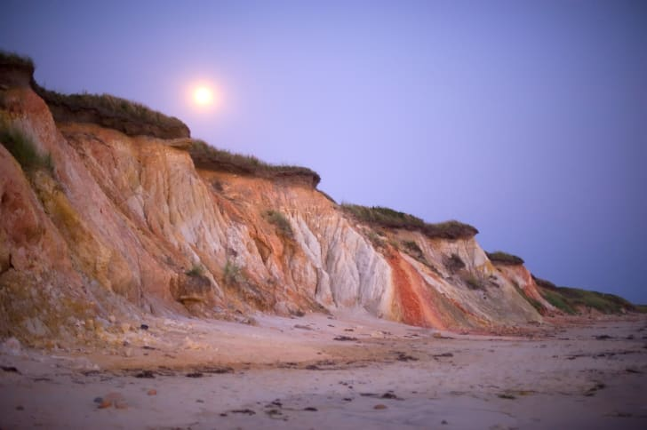 Colorful cliffs at dusk with a rising moon in the background