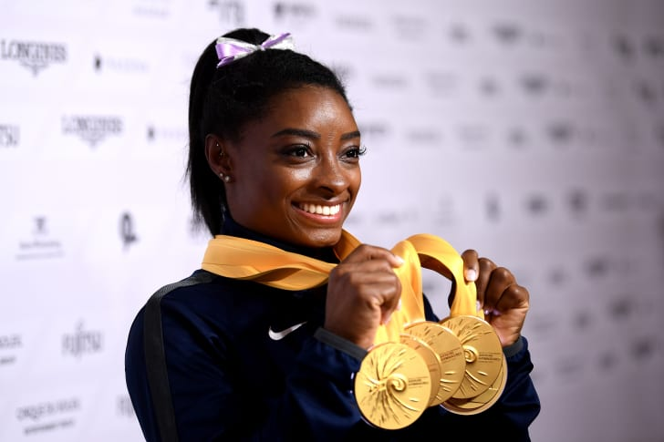 Simone Biles of The United States poses for photos with her multiple gold medals during day 10 of the 49th FIG Artistic Gymnastics World Championships at Hanns-Martin-Schleyer-Halle on October 13, 2019 in Stuttgart, Germany
