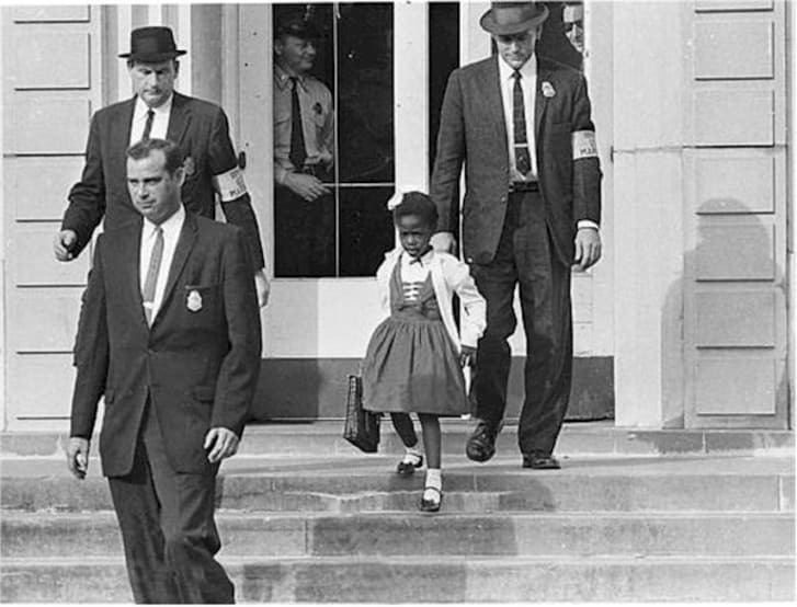 "William Frantz Elementary School, New Orleans, 1960. ""After a Federal court ordered the desegregation of schools in the South, U.S. Marshals escorted a young Black girl, Ruby Bridges, to school."""