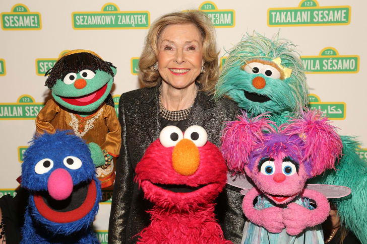 Joan Ganz Cooney and the Sesame Street Muppets.
