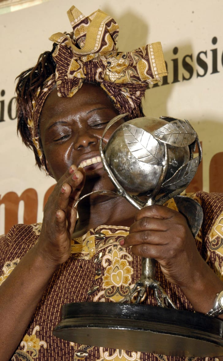 A woman smiling while holding a trophy