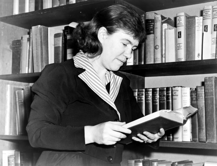 Black and white image of a woman reading a book
