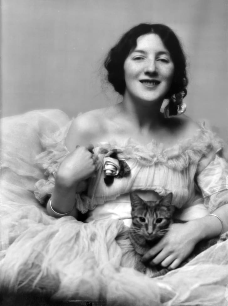 Portrait photo of a woman in a fancy dress holding a cat