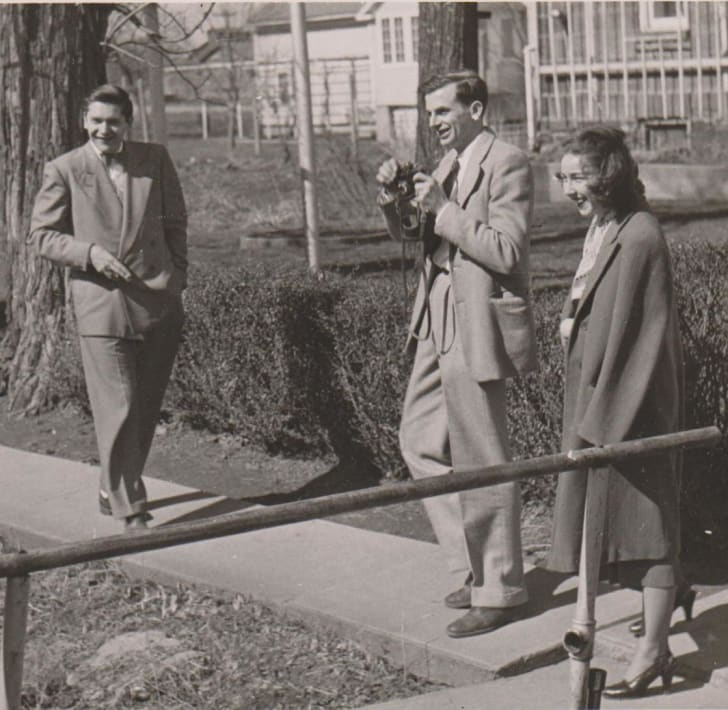 Black and white photo of a woman walking with two men