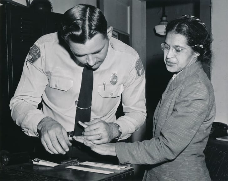 A woman gets fingerprinted by a police officer