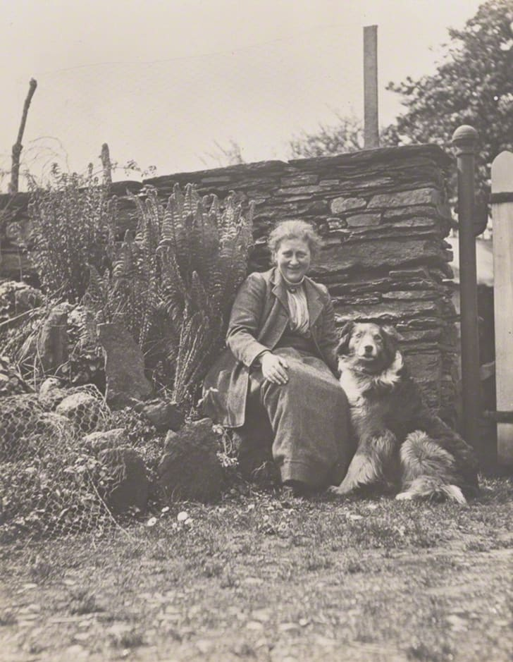 A woman sitting outside with her dog
