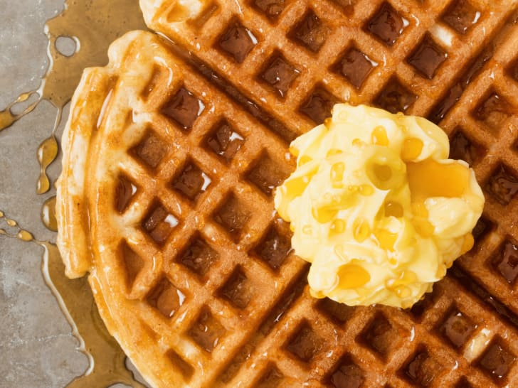 A waffle covered in butter and syrup