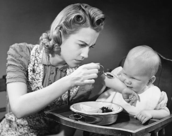 Vintage style photo of a mother trying to feed her fussy baby